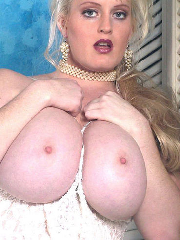 Fat blonde Heather Michaels dressed in white shows off her massive tits and snatch