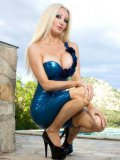 Fetish sex bomb Saffron Taylor erotically posing in front of a pool on a sunny day in blue latex.