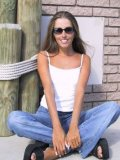 Slim playful girl Lori Anderson in blue jeans and white top plays with her arm hair in the sun
