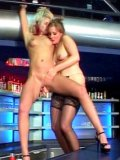 Naked blonde Peggy Sue gets her smooth pussy dildo fucked by latex-clad redhead at a bar