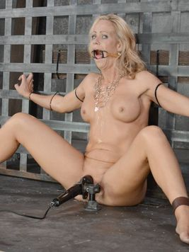 Simone Sonay tied to a cage and having her slit stimulated during bondage cock sucking.