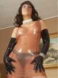 Stella Van Gent naked and sliding her hands while wearing noting but her see-through latex gown.