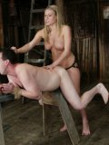 Topless Harmony Rose in boots shows her bald pussy as she drills ass of her slave with dildo