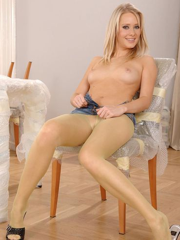 Tall blonde babe Deni with long legs poses in see through yellow pantyhose