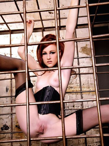 Hollis Ireland in black stockings and red shoes spreads her legs wide in cage