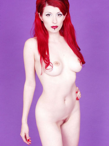 Redhead Yolanda poses fully naked after taking off her white corset and long silver skirt