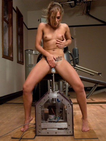 Small titted girl Dakoda Brookes with tattoo above her bald pussy uses fucking machine at the gym