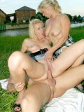 Anna Lena shares a hard cock with another middle-aged blonde in the grass in public place