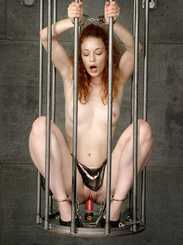 Handcuffed skinny redhead Justine Joli plays with her tight pussy behind the bars