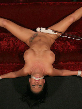 Jayden Jaymes has her clit vibrated with the magic wand as her hands and legs are tied to the couch