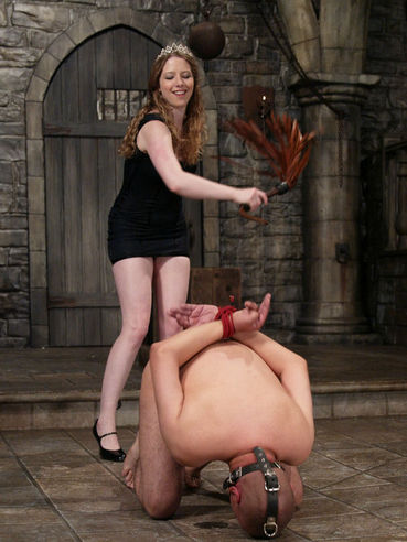 Domina Princess Kali in black dress fucks mouth of nude Maximus with foot and dildo