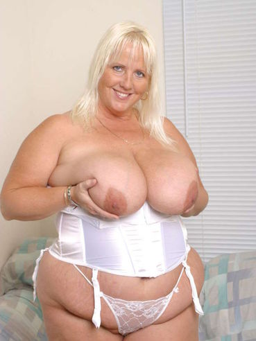 Plump mature blonde Daphne Stone poses in white lingerie making no secret of her giant tits