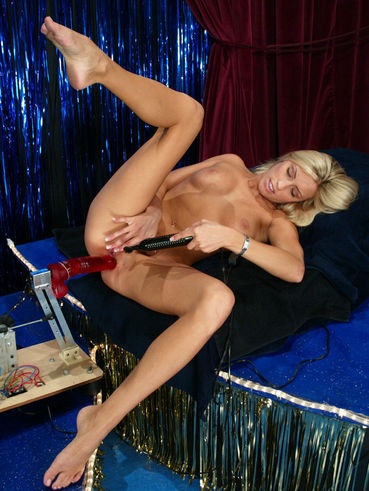 Cassie Young with long sexy legs and tight bald pussy enjoys red robotic dildo in a blue room