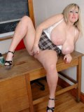 Bulky blonde Leah Jayne in skirt and top exposes her snatch and giant tits in the classroom