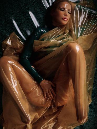 Flirtatious fetish lady Bianca Beauchamp dressed in latex poses in the semi-dark