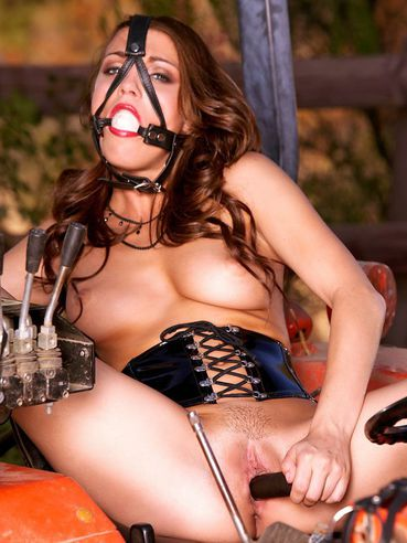 Ball gagged babe Charlie Laine in corset and boots dildos her snatch outdoors