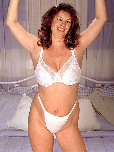 Smiling chubby redhead Roberta Canyon loves posing in white bra and panties