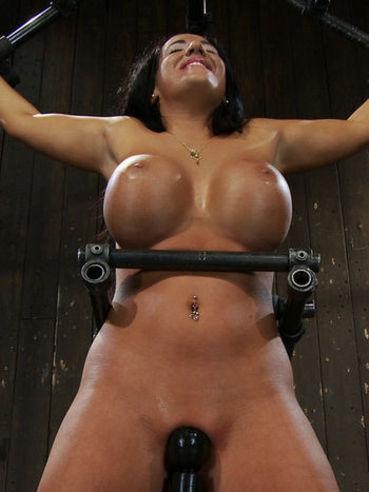 Spreadeagled big racked slave brunette Richelle Ryan loses her clothes in metal restraints.