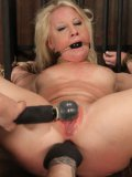 Clothed mater plays with shaved pussy of nude slave blonde Kimmy Olsen in the dungeon
