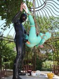 Latex Lucy in a teal, plasticky outfit tied up and hanging in roped during bondage.