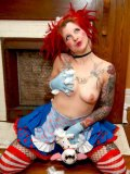 Inked up redhead Hel Inferna in costume and latex gloves goes topless and touches her tits